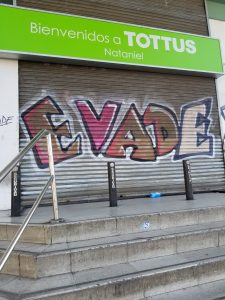 photo of supermarket security door with EVADE graffiti