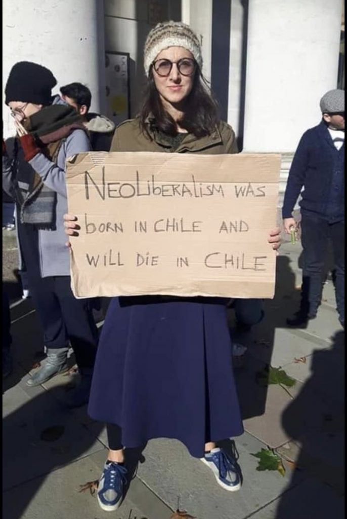 "photo of woman holding cardboard sign saying ""neoliberalism was born in Chile and will die in Chile"""