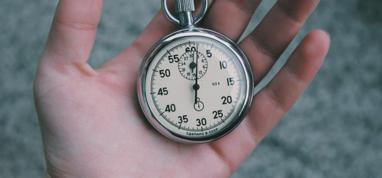 human hand holding analog stopwatch