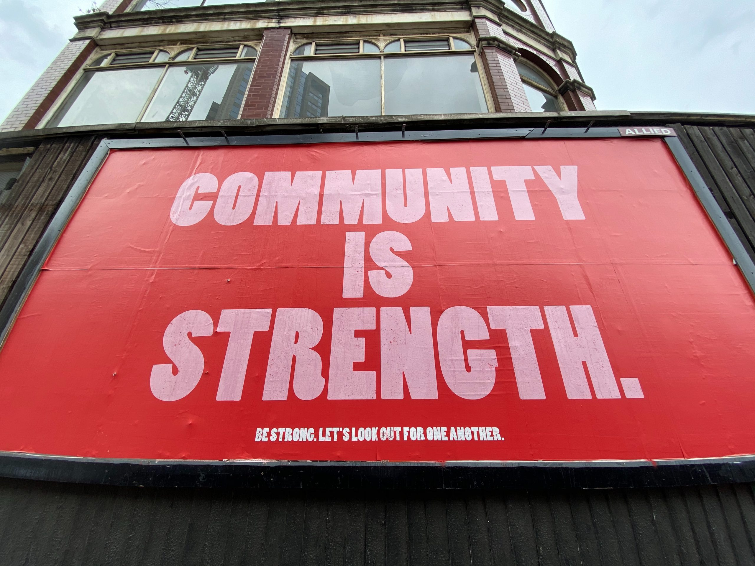 billboard white words on red background community is strength
